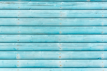 Section of weathered turquoise blue panelling from a beach hut, suitable for backgrounds of beach, seaside and summer holiday themes.