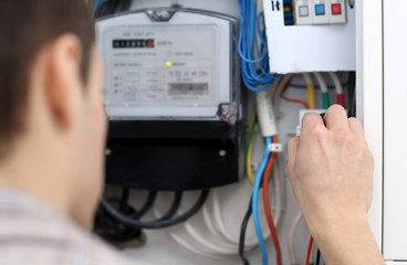 Young electrician checking voltage in fuse board