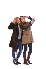 Two young women taking selfie in their winter clothes isolated on white