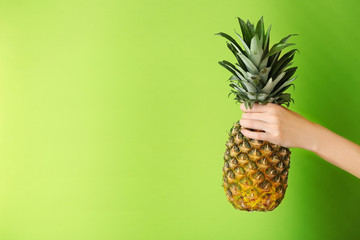 Female hand holding ripe pineapple on green background