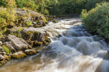Summer landscape on a stormy river full of rapids in Karelia on Ladoga. Asilansky rapids on the river Asilanyoki