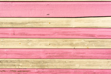 Section of weathered pink and white wood panelling from a beach hut, suitable for backgrounds of beach, seaside and summer holiday themes.