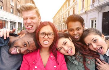 Multiracial best friends taking selfie outdoors in urban contest