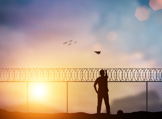 Silhouette of a prisoner behind a barbed wire fence, throw paper airplanes to fight outside the barbed wire fence over blurred nature. Concept Freedom, independent business, independent thinking.