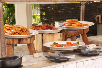 Breakfast bar buffet at restaurant. Sausage, bacon and baked tom