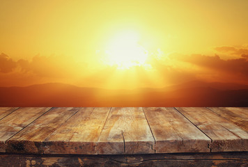 wood board table in front of golden sunset. product display background