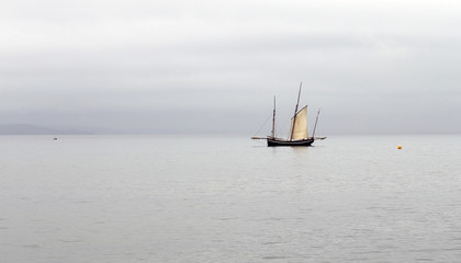 Ancient fishing boat, a Cornish lugger, becalmed off Newlyn, Cornwall, England, UK.