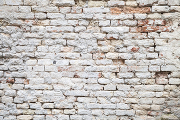 Old red brick wall with white paint layer