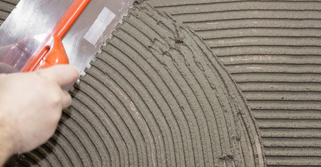 Worker tiler put cement
