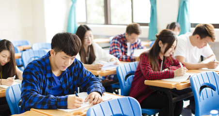 group of young students writing notes in the classroom