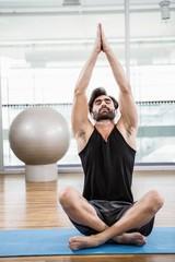 Handsome man doing yoga on mat