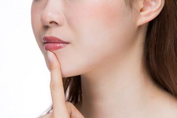 唇を指差す女性