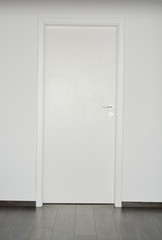 White closed door with silver doorknob on white wall background and parquet floor