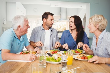 Family discussing while sitting at dining table