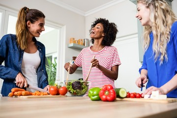 Young female friends laughing while preparing food