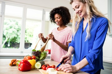 Cheerful female friends preparing food at table