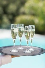 Cropped hands of waiter holding champagne flutes tray