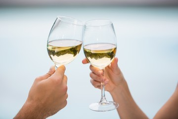 Cropped hands of couple toasting white wine