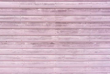 Section of textured pink wood panelling from a seaside beach hut. Could be used as a background to illustrate beach and summer holiday themes.