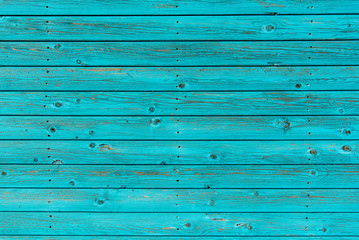 Section of textured turquoise wood panelling from a seaside beach hut. Could be used as a background to illustrate beach and summer holiday themes.