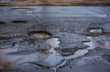 bad road with holes and puddles