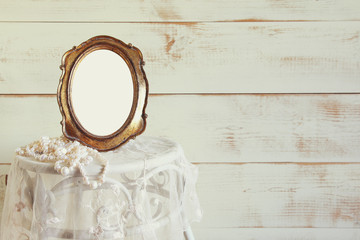 Antique blank vintage style frame and white pearls on elegant table. template, ready to put photography. vintage filtered