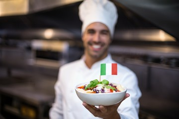 Handsome chef presenting meal with italian flag