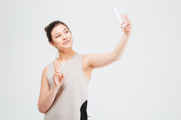 Business woman taking selfie with smartphone and showing peace gesture