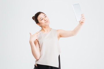Business woman taking selfie with tablet and making duck face