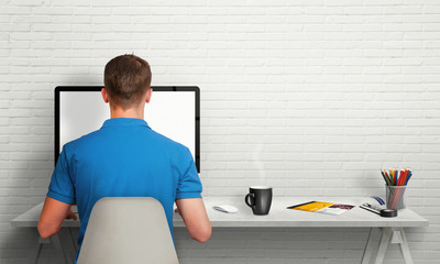 Wall Mural - Man working on computer with isolated screen in office interior. Work desk with keyboard, mouse, cup of coffee, paper, pencils. Free space on wall for text.