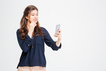 Attractive happy young woman taking selfie with mobile phone