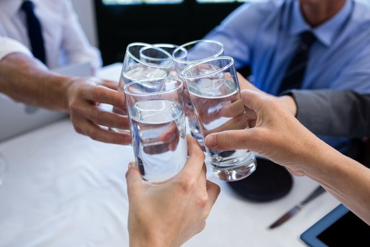 Group of businesspeople toasting glass of water in restaurant