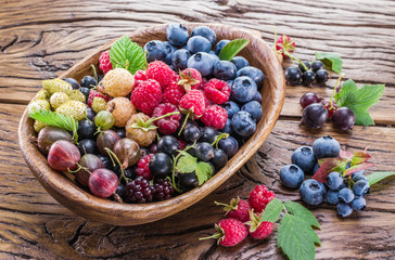 Ripe berries in the wooden bowl.