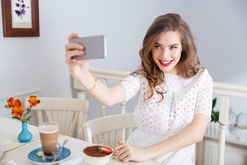 Smiling beautiful woman taking selfie with smartphone sitting in cafe
