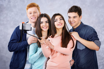 Teenager friends making photo by their self with mobile phone on grey background on grey background
