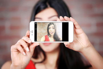 Young attractive girl making photo by her self with mobile phone on brick wall background, close up