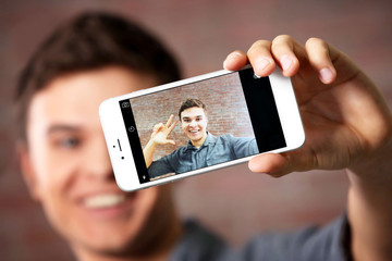Young handsome boy making photo by his self with mobile phone on brick wall background, close up