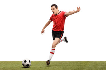 Young football player kicking a ball