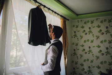 Stylish and handsome groom in waistcoat tying his bow-tie in the morning of the wedding day. Groom with beard