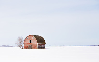 An old weathered red barn with hayloft in a barren countryside winter landscape