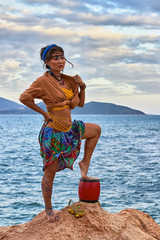 Woman shaman standing on drum, mountain sea. Ethnic fashion photoshoot.
