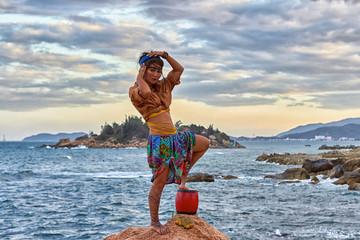 Woman shaman standing on drum, mountain sea. Ethnic fashion photoshoot.