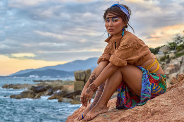 Asian woman, bright makeup, boho style, ethnic fashion, near sea.