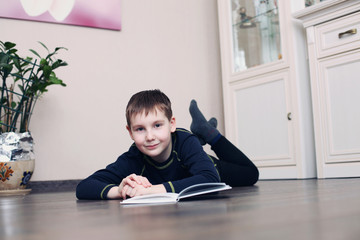 child reads the book on a floor