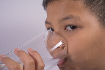 Young Asian boy drink water from a glass