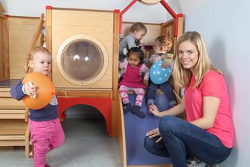 Erzieherin mit 4 Kindern an Spielgerät 2