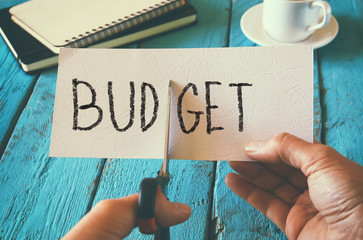 man hand holding card with the word budget. cutting budget and costs concept. retro style image