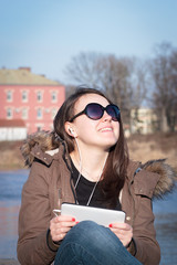 Pretty young girl / woman with black sunglasses listening music