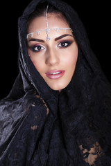 Beautiful Woman in Middle Eastern Niqab veil on isolated black b