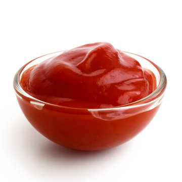 Small glass condiment bowl of red tomato sauce ketchup.